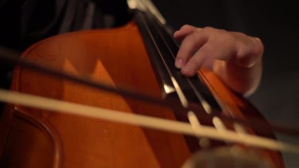 Männlicher Cellist, der im Dunkeln auf der Bühne Cello spielt. Kiew. Ukraine