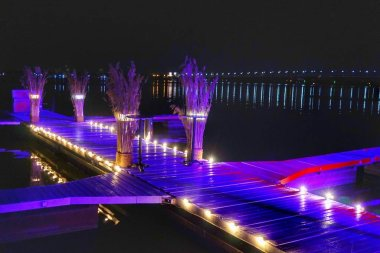 Night illumination of a pier on the river water