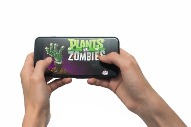 Samara, Russia -07, 29, 2019: A young guy plays a plants vs. zombies game on Iphone 8 Plus. Teenage boy holding a phone in his hands with a game plants vs zombies mobile on a white background