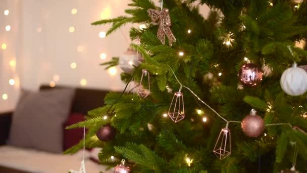 Karácsonyi háttér meleg családias hangulatban. A karácsonyfát arany, burgundi és barna golyók díszítik. Füzérek és játékok a lucfenyőn egy könnyű, meleg belső térben. Zárókeret