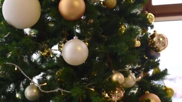 Vánoční pozadí v teplé domácké atmosféře. Vánoční stromek je zdoben zlatými, bílými a hnědými kuličkami. girlandy a hračky na smrku v lehkém teplém interiéru. Zavřít rámec