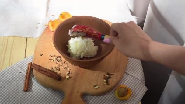Dívka dává čerstvě vařené rýžové mléko kaše v jílovém nádobí
