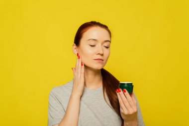A red head girl is applying cream on the face . A girl smears face cream on the yellow background.