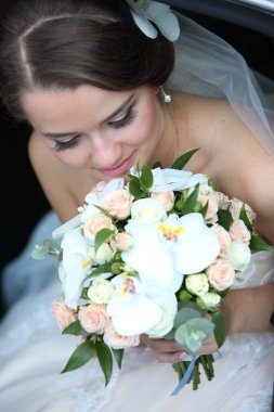 Cute bride with a bouquet in her hand in a car in the back seat