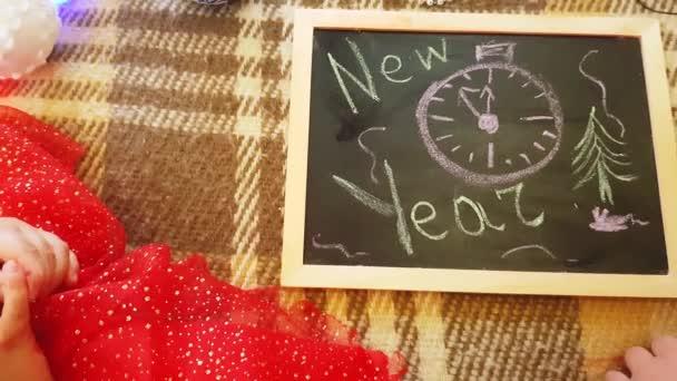 Máma a dcera kreslí novoroční atributy na tabuli. Máma a dcera kreslí vánoční stromek. Novoroční téma: maminka a dcera malovat nový rok v domácí slavnostní atmosféře.