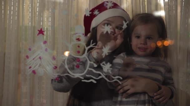 Mutter und Tochter malen einen Schneemann und einen Weihnachtsbaum mit Farben auf eine Fensterscheibe. Zeichnung mit Acryl auf Glas.