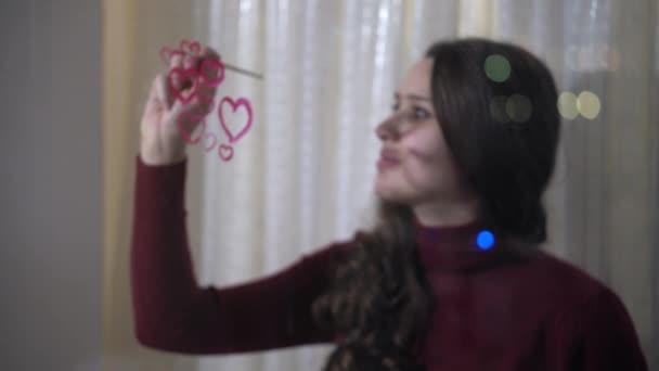 schönes Mädchen malt ein Herz auf Glas