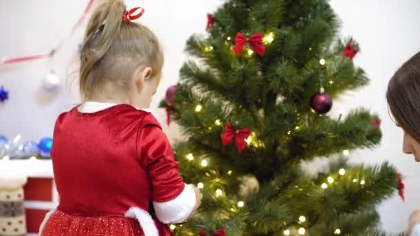 dítě a těhotná maminka pověsit červený míč hračka na vánoční stromek. Šťastné dětství. dítě a matka zdobí strom s vánočními míčky. malé dítě a rodič hrají u vánočního stromečku.