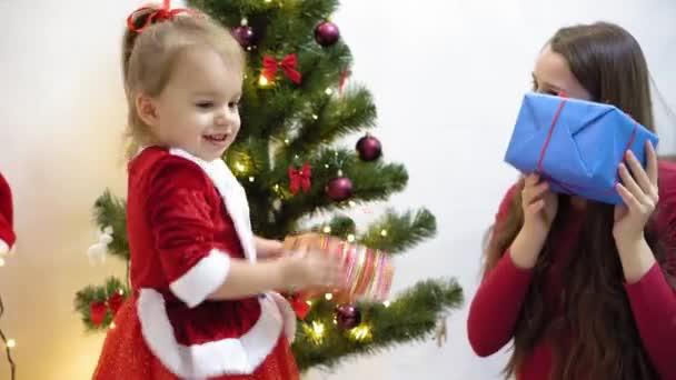 Baby und schwangere Mutter hängen rotes Kugelspielzeug an den Weihnachtsbaum. Glückliche Kindheit. Kind und Mutter schmücken Baum mit Weihnachtskugeln. Kleines Kind und ein Elternteil spielen am Weihnachtsbaum.