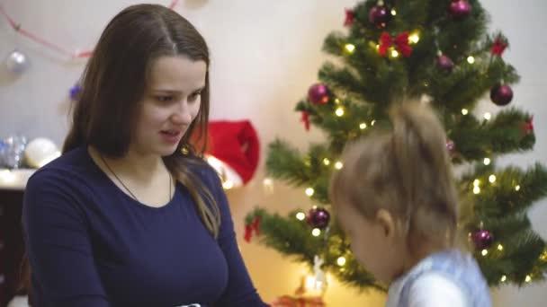 Zwei Kinder betasten und küssen den Bauch einer schwangeren Mutter