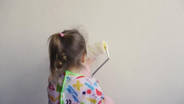 Opravy, renovace, domov, rodina, dětství, rodičovství, otcovství, samostatnost, koncepce karantény - zblízka malá 3-letá holčička hrající si s válečkem, malování stěn v bytě bílá barva.