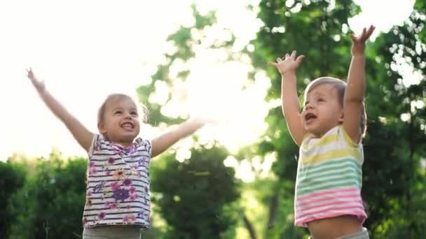 pojetí dětství, rodiny, životního stylu, zábavy a lidí - dvě malé děti stejného věku chlapec a dívka trhají trávu a zvracejí v parku na pozadí západu slunce. zpomalený pohyb