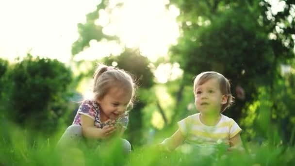 dětství, rodina, životní styl, zábava a lidé koncept - dvě malé děti stejného věku, chlapec a dívka trhání trávy a zvracet v parku na pozadí západu slunce.