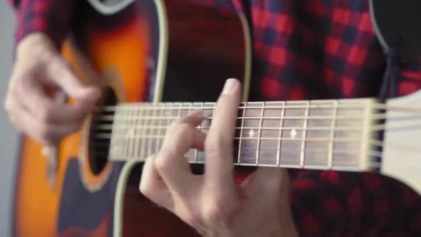 hudba, tvořivost, koncert, koncepce sebeizolace. Detailní záběr rukou mladého muže hrajícího na akustickou kytaru v měkkém ohnisku. Prsty třídí struny stiskem akordů na prknech prkna.
