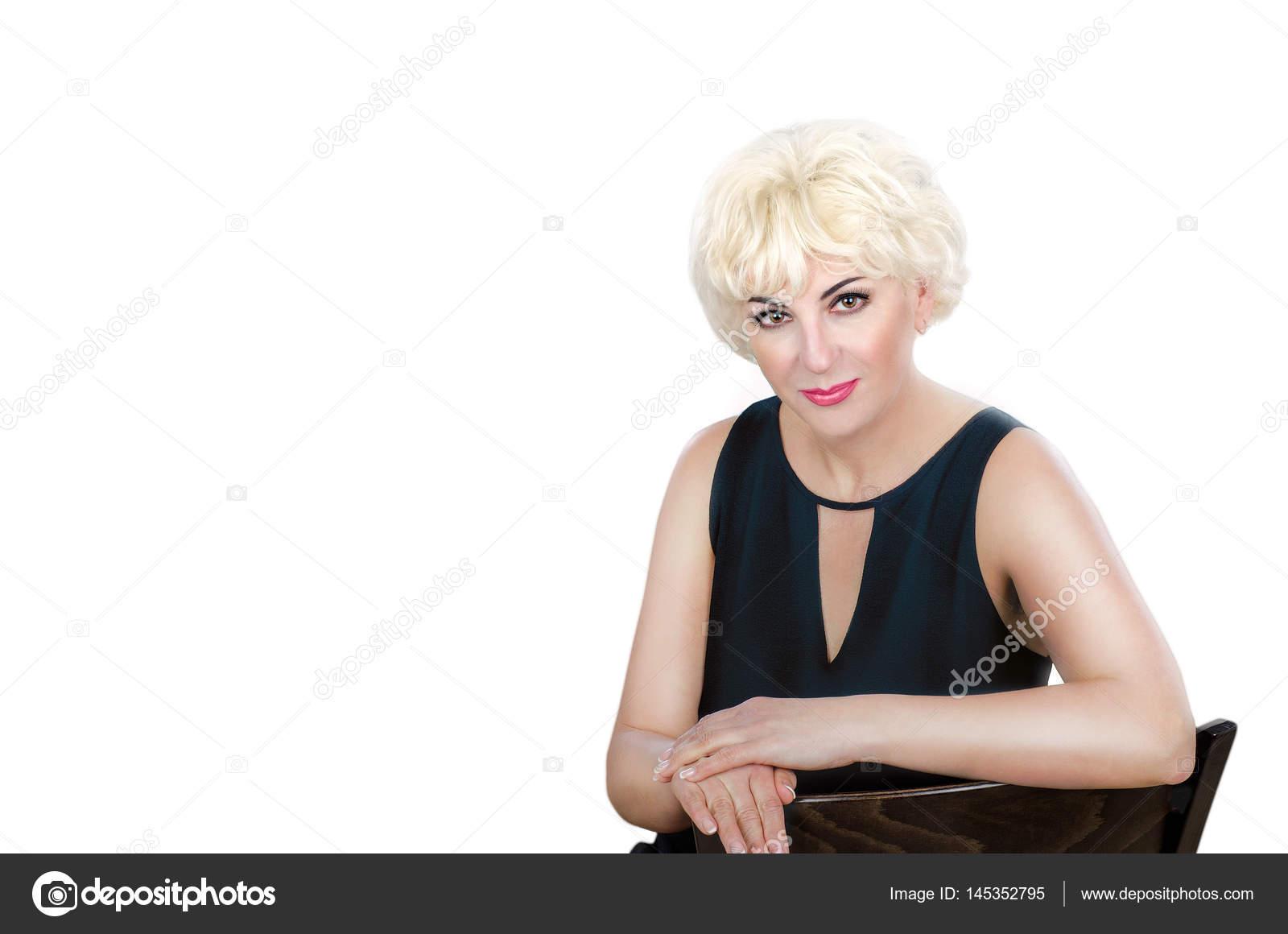 Reife blonde Haare Frau sitzt schaut die Kamera ausdrücklich ...