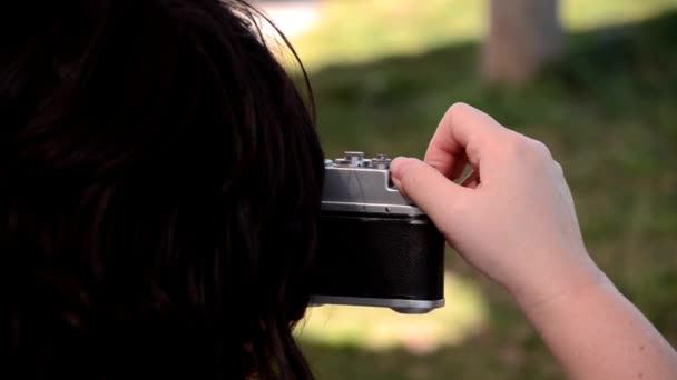 Headshot of woman photographing with old camera