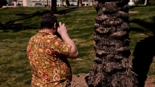 Mann fotografiert im aloha Hemd ein mit Retro-Kamera im Stadtpark
