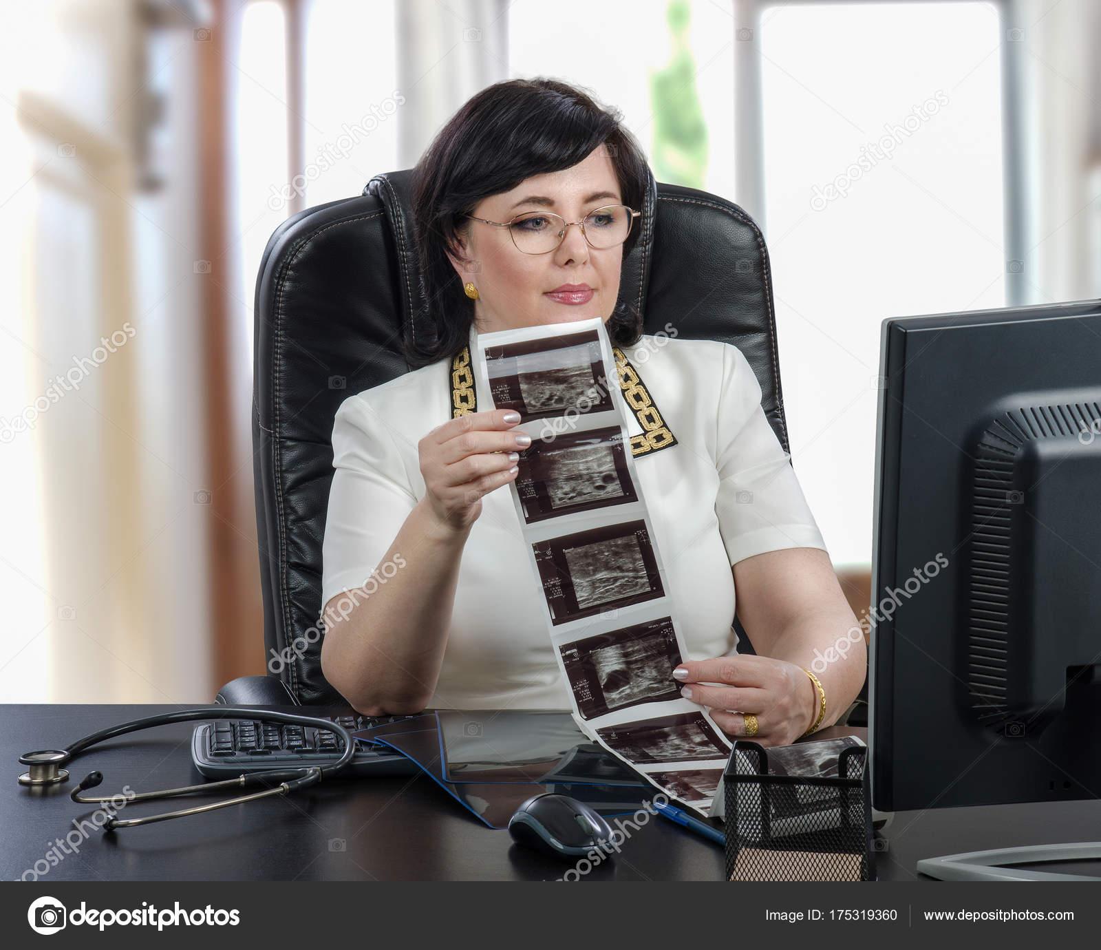 2a6a9f234eaf Τηλεϊατρική ιατρός ντυμένος μια λευκή μπλούζα που κάθεται στο μαύρο γραφείο  στο γραφείο — Εικόνα από ...
