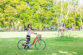 Young asian women with bicycle on green meadow