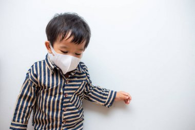 Portrait of asian baby boy wearing dust mask protect for PM2.5 and coronavirus or covid-19 infectious disease on white background. Facial hygienic mask for virus safety