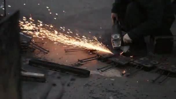 tovární dělník leští tyčové prvky s úhlovou bruskou