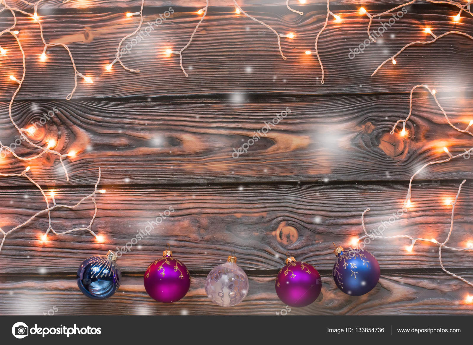 Christmas Wooden Background With Lights Snow And Ornaments Stock Photo