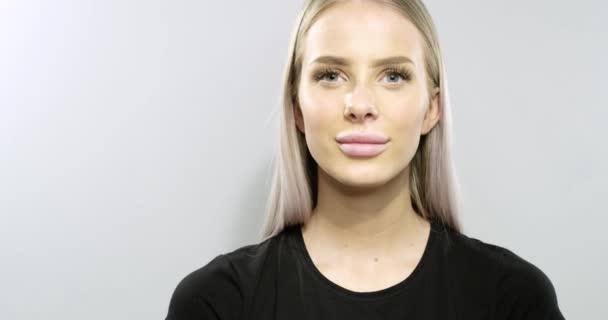 Mosolygó fiatal szőke nő mutatja, névjegykártya