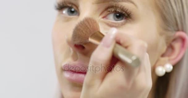 Közeli kép: egy gyönyörű fiatal nő alkalmazása száraz kozmetikai tonális Alapítvány