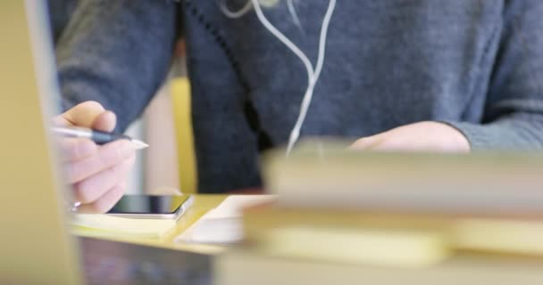 Close-up of a female student working at school library