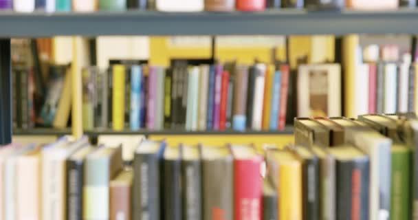 Studentka hledá knihu ve školní knihovně
