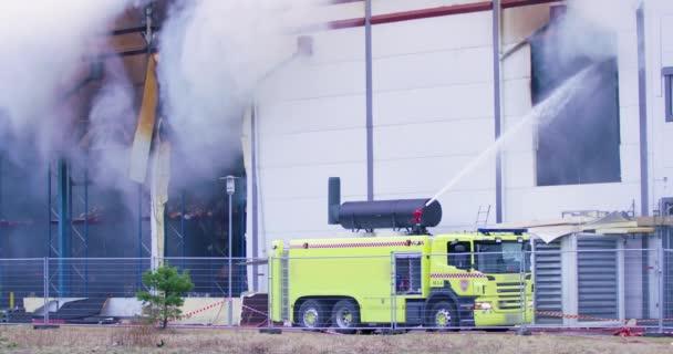 Hasičské auto se snaží získat kontrolu nad ohněm v průmyslové budovy