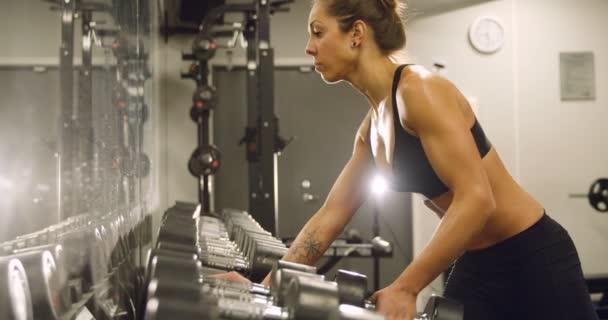 Vyhrazený žena školení a tréninků v posilovně fitness