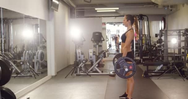 Těžké pracovní žena školení deadlifts s těžké váhy v posilovně fitness