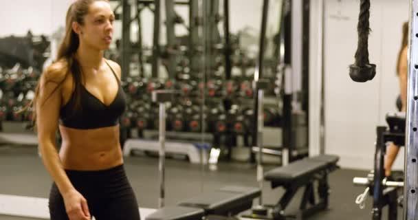 Sportovní žena trénink triceps svaly tahání kabelu stroje v tělocvičně