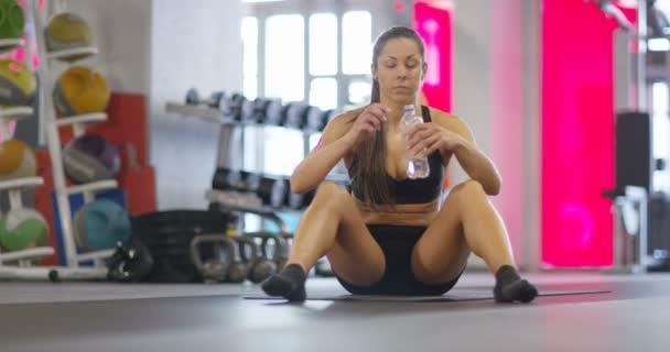 Portrét klidových fitness žena sedící na podlaze pitné vody