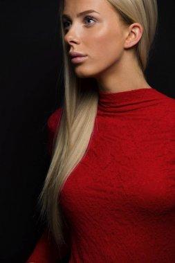Dark portrait of a pretty blonde woman in red dress on black bakground