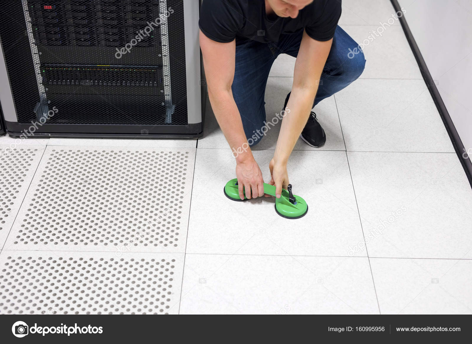 Engineer Lifting Floor Tile Using Vacuum Suction Cups In Datacen