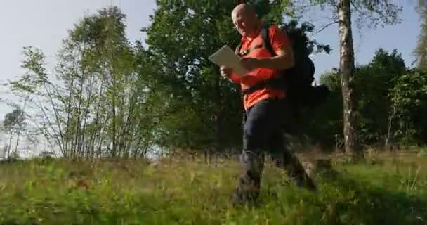 Active man hiker navigate using map and compass in beautiful forest at sunset