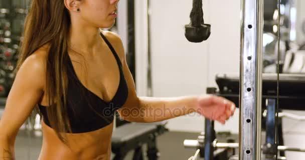 Detail zaměřené ženy trénink triceps svalů tahání kabelu stroje v tělocvičně