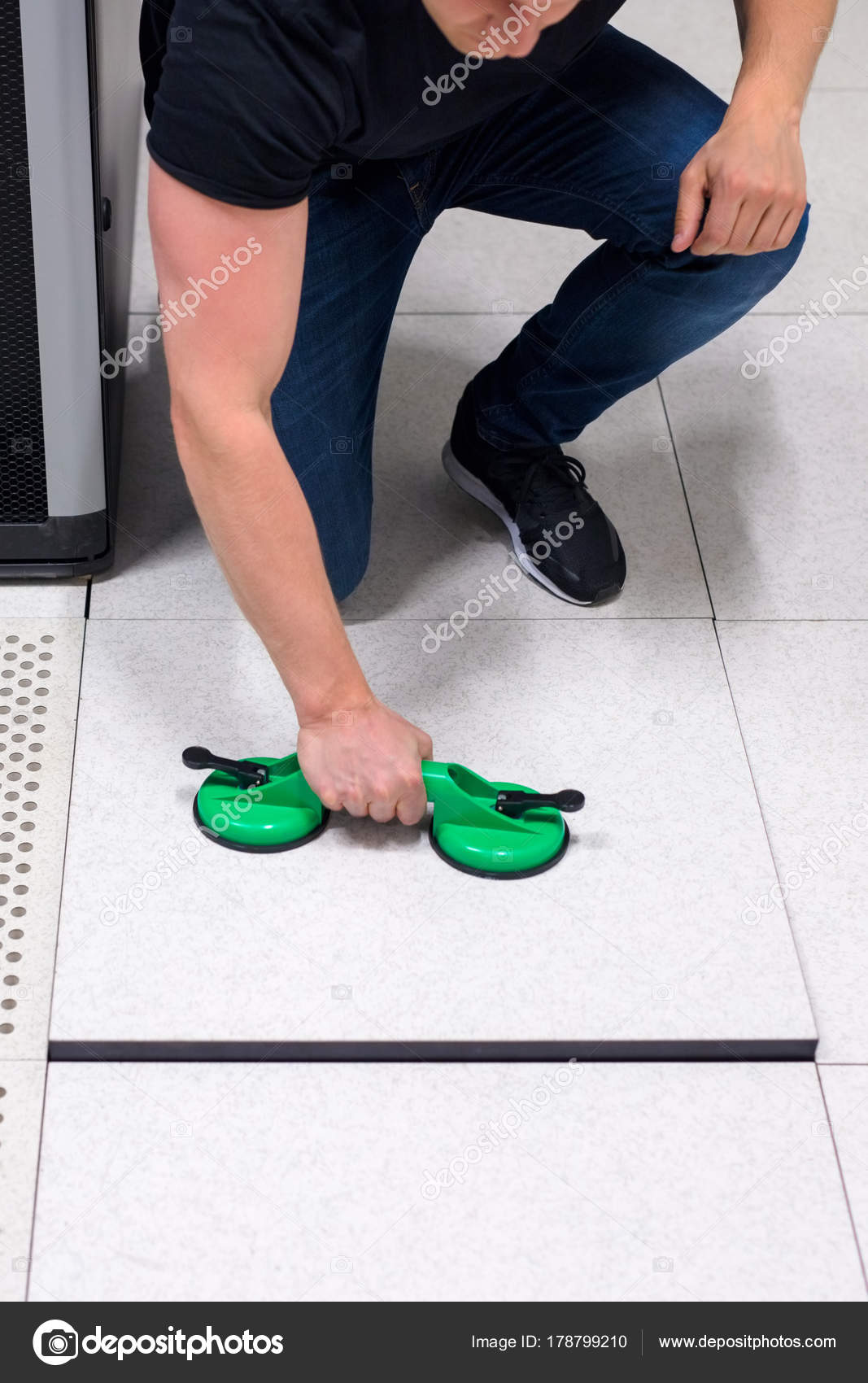 Computer Engineer Pulling Floor Tile Using Suction Cups In Datac