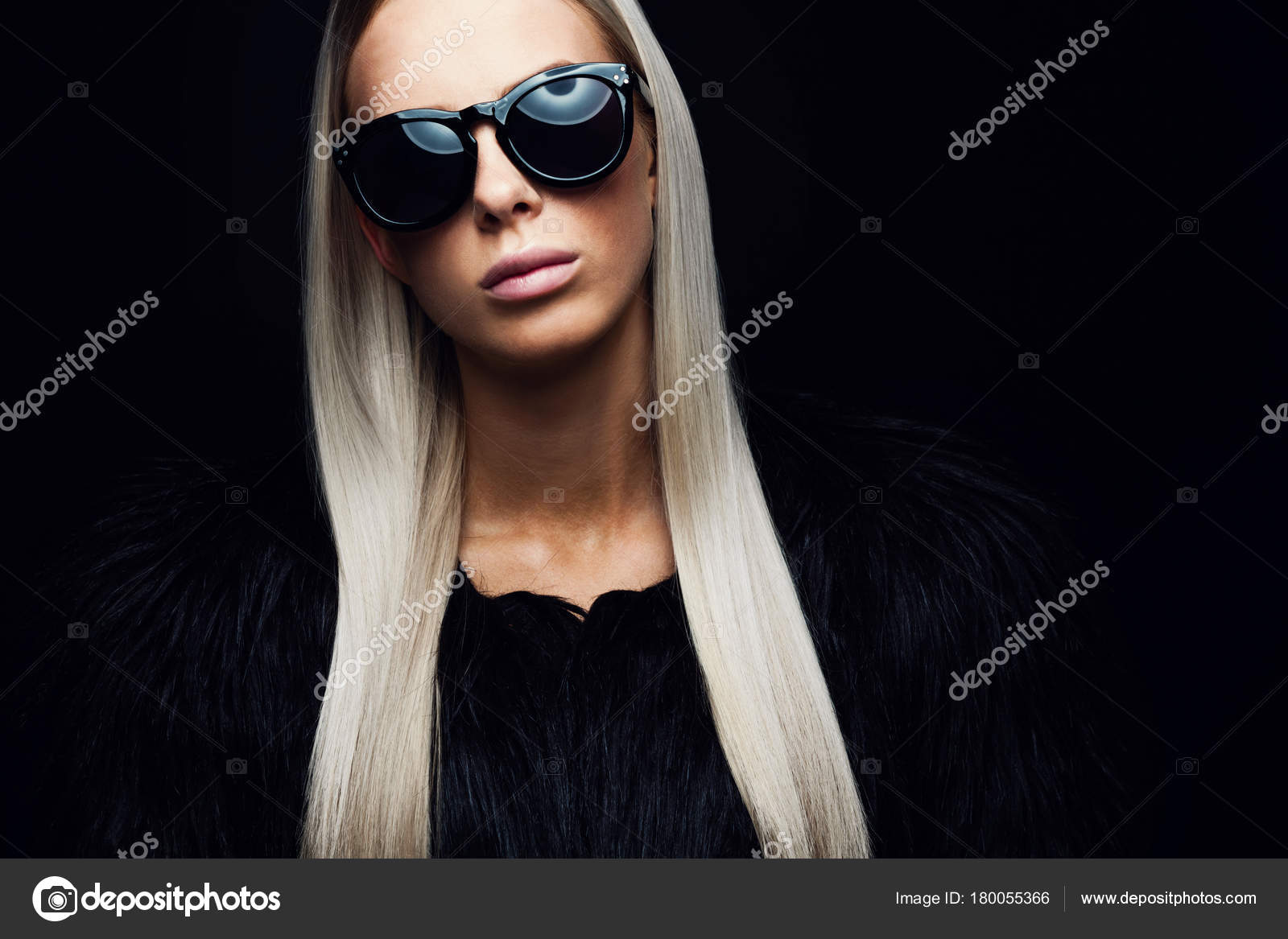 Beautiful young fashion woman with long blonde hair and black furry design  jacket. Cool looking girl with glasses in studio. Black backround.