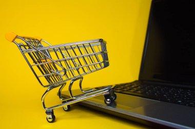 E-Commerce. Online shopping, shopping cart on laptop keyboard.