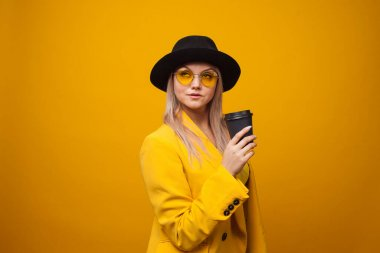 Stylish trendy young woman in bright clothes on a yellow background. Cool blonde