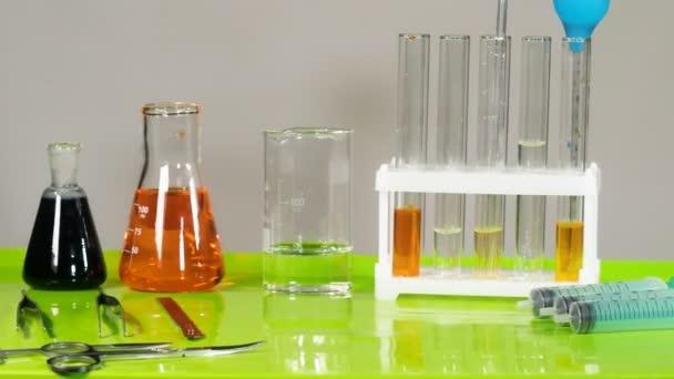 Vizsgálócsövek, lombikok és egyéb eszközök állnak az asztalon a laboratóriumban.