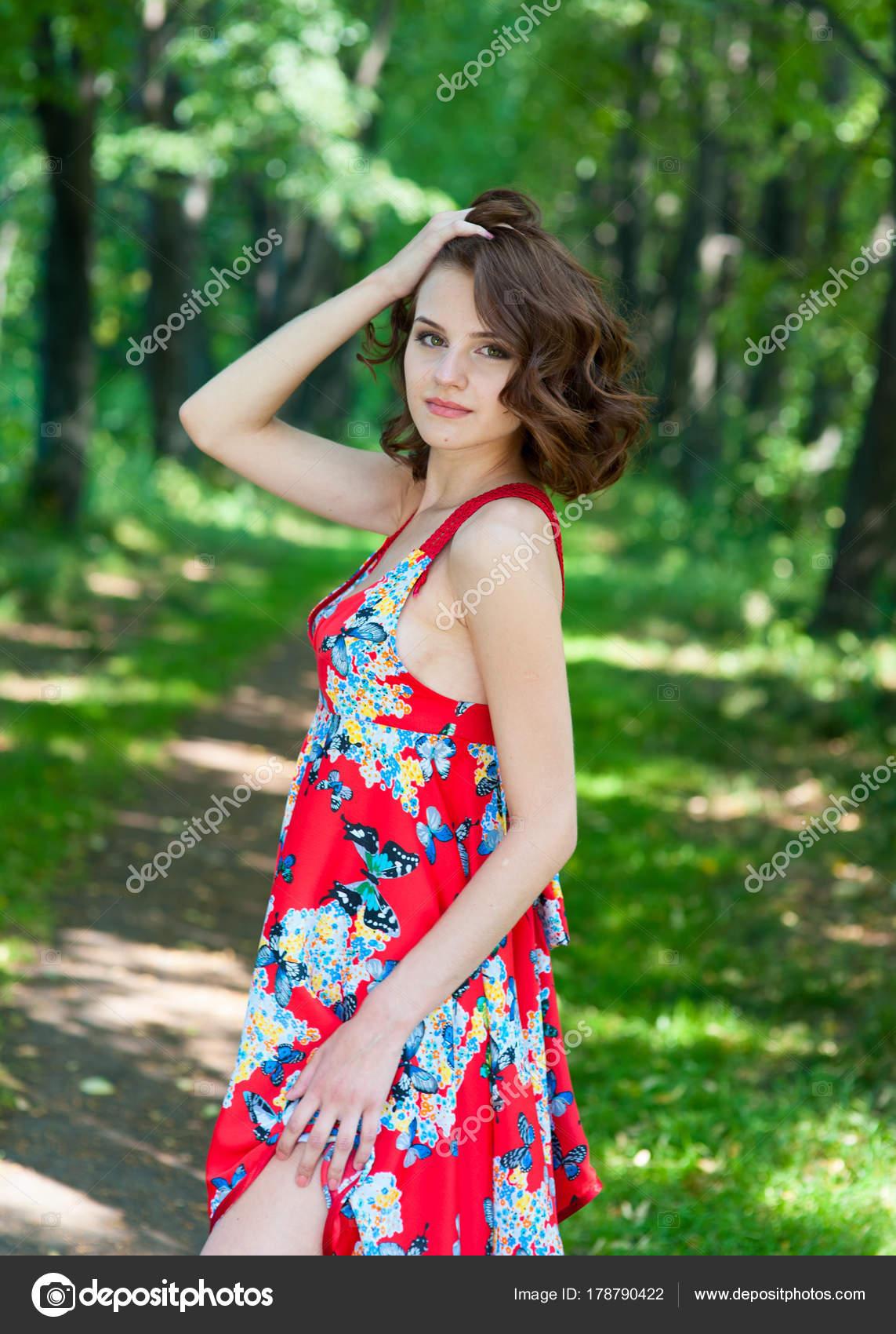 cbd66ed43b99ef Jonge brunette meisje in de rode jurk poseren op steegje in zomer park  tegen bomen —