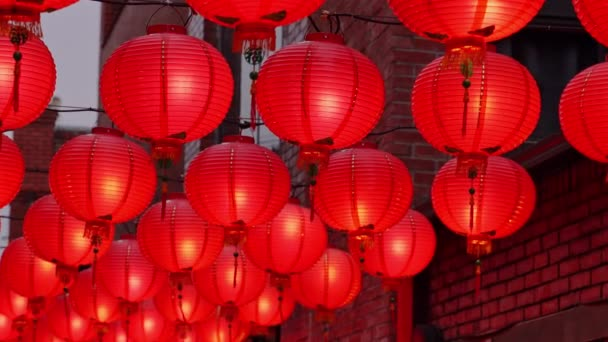 Walking on a Chinese traditional street at night with beautiful round red lantern hanging and swaying, concept of lunar new year festival, close up. The undering word means blessing.