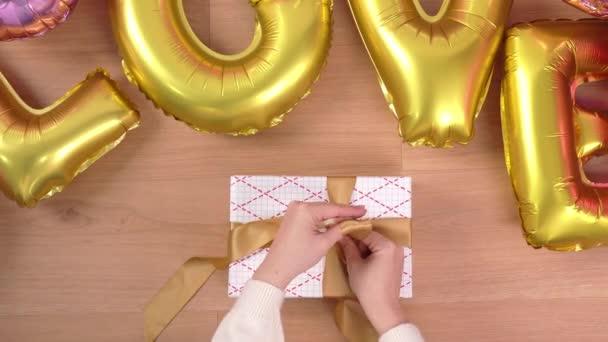 Mladá žena v bílém svetru je balení, balení krásné dárkové krabice pro přípravu dovolené se zlatým balónem, pomocí obalu a lana vázat luk-uzel, životní styl, horní pohled.