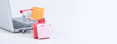 Online shopping. Mini shop cart trolley with colorful paper bags over a laptop computer on white table background, buying at home concept, close up