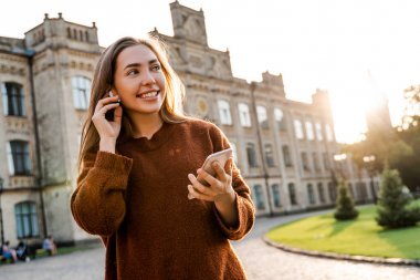 Candid charming pretty teen woman walking in park and listening to music, connected to her smart mobile phone, smiling and having relax time alone, using modern technology, active people lifestyle