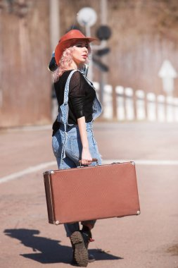Young traveling woman with a suitcase hitchhiking on the road